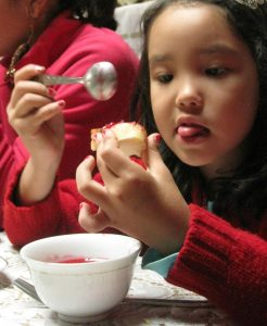 young central asian girl putting jam in her tea and on her bread